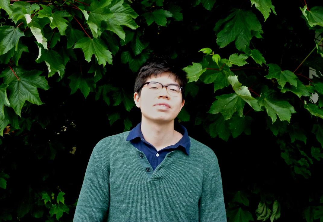 Head, torso and shoulders of Will standing against thick green foliage. He is wearing a green jumper, with an open necked dark blue shirt. Hair is dark, wears glasses, head angled up the way appraisingly, a relaxed but serious expression. He is in his early twenties to look at him, and the Indonesian heritage is obvious in his face.