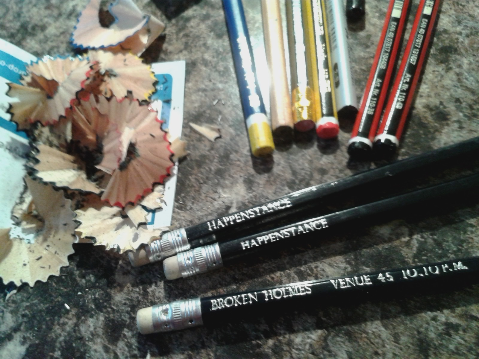 Full colour photo of a set of pencils, at different angles, and different types, with a sharpener and lots of sharpened pencil shavings.