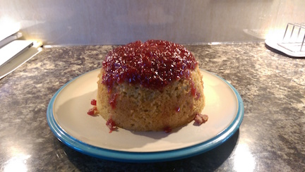 A jam-topped steamed pudding sitting on a blue-rimmed plage.