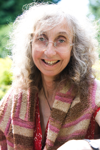Head and shoulders photo of author smiling broady. She has a colourful shawl around her shoulders, pink and brown. Her hair is shoulder length and irradiated by sunlight.