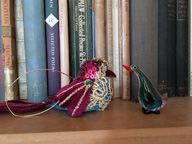 Colour photo of bookshelf with two little birds, one a Xmas decoration and one glass. The birds are looking at each other. Behind them a row of book spines, various colours.
