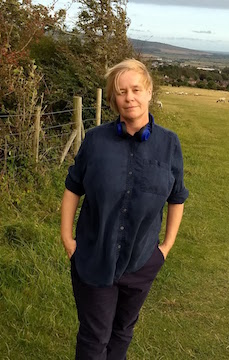the full colour pic shows the author standing outside, in a dark blue shirt rolled up to the elbows, both hands in the pockets of her dark trousers. Her hair is blonde and blown to one side. Her face is calm and serene, but not smiling. She's looking straight at the viewer. Behind her are the rolling fields and hills of the South Downs, as well as a fence with some trees behind it.