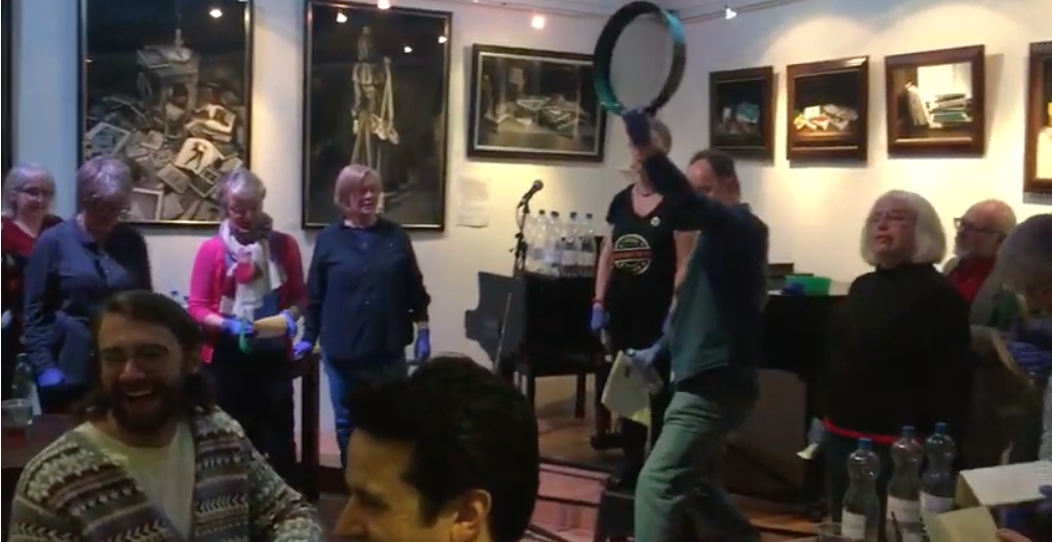 Freeze frame from teh film of the HappenStance flashmob performing Lear's The Jumblies. You can see Matthew Stewart at the front brandishing a large green sieve with various others standing around grinning, most of them wearing blue surgical gloves. A few diners near the front are chuckling.