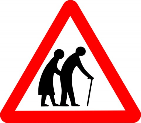 Elderly people crossing road sign, depicting two old people. The old man is in front with a stick. The old woman stoops alongjust behind him. It's quite a sexist sign!