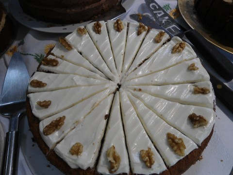 Close up of iced carrot cake, decorated with walnuts and sliced ready to serve. About twenty slices, I'd say. It was delicious.