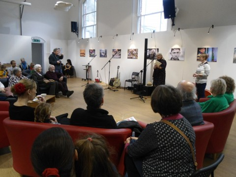 Annie Fisher reading with microphone to an audience in a large hall, comfy seats in a big semi circle and light from big overhead windows. Behind her, along the white wall a striking exhibition of photographs.