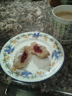 Mug of tea, and china plate with raspberry bun cut open to reveal red jam inside