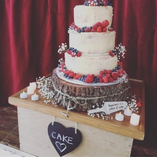 Full colour photo of wedding cake surrounded by soft fruit, strawberries, blueberries, raspberries. The cake slice has lettering on it that reads Happiness is a piece of cake.