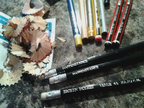 Full colour photo of pencils and wooden sharpenings. Three black pencils with erasers at the ends are visible. Two of them have HAPPENSTANCE in silver caps. The third says BROKEN HOLMES VENUE 45 (Holmes as in Sherlock).