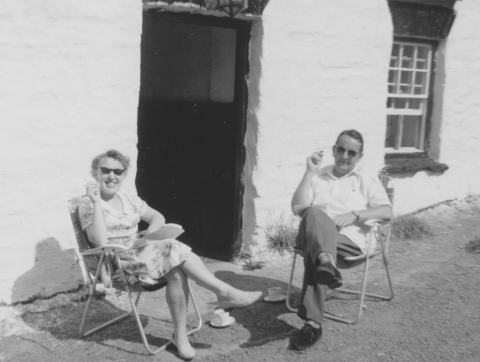 Monchrome photo of a youngish couple sitting on two folding chairs outside the door of a holiday cottage. Each has a cup and saucer on the ground beside the chair. Each has a cigarette in the right hand. Both are wearing dark glasses and smiles. It must be a very warm day because the short haired guy (my father) is wearing sunglasses, and so is my mother. This picture was taken in South Wales.