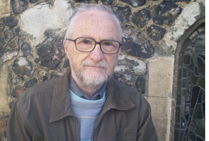 Full colour head and shoulders of the poet wearing a casual brown jacket, turtle neck jumper (pale blue) with grey shirt beneath. He has dark framed spectacles, grey hair swept back from his forehead, which is slightly freckled, and a short grey beard. He is looking at the photographer appraisingly and could be wearing the beginning of a smile. Behind him is what seems to be the wall of a church, with a fragment of stained glass window to his left.