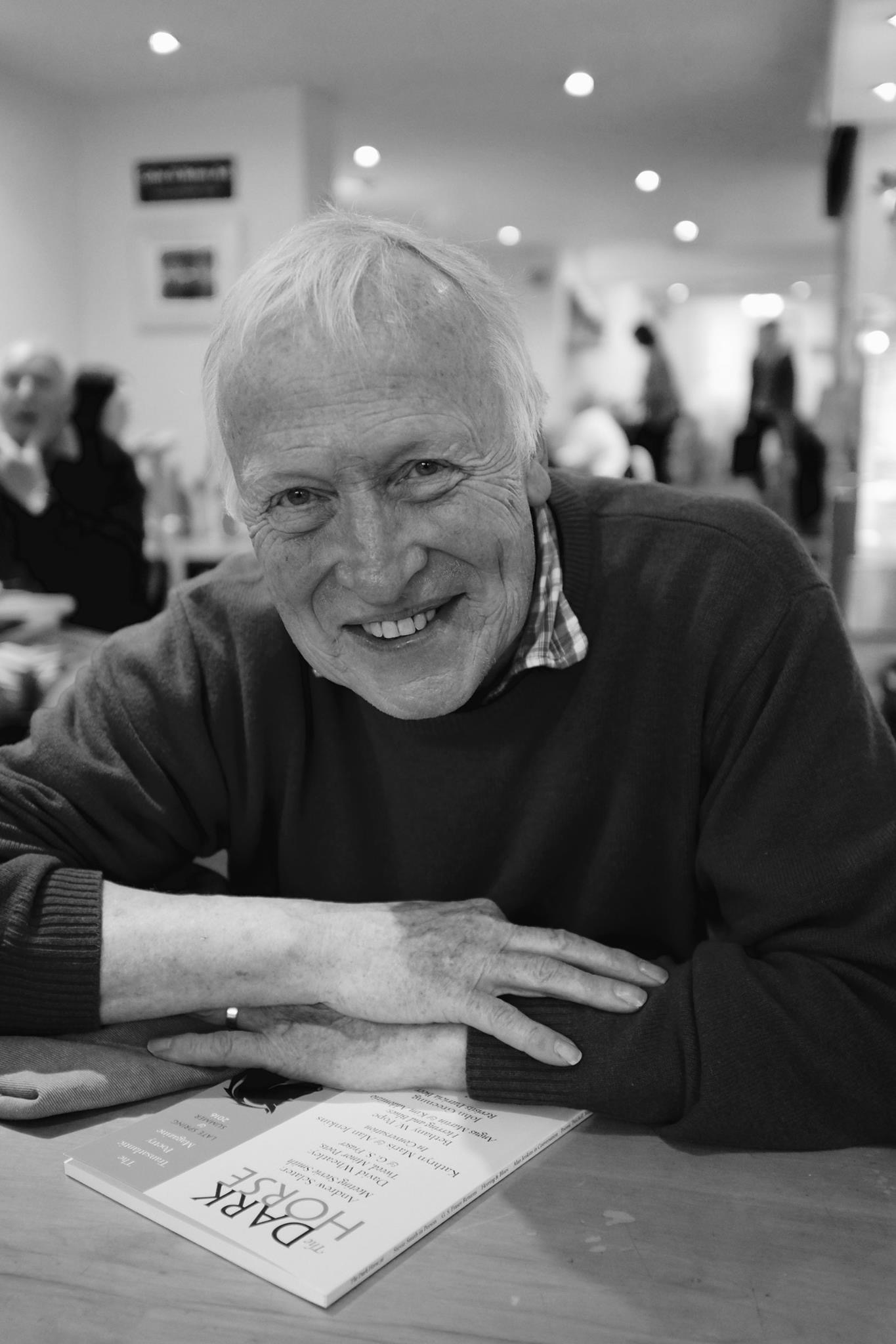 Photo of Andrew leaning forward over a table, his arms folded on the surface. A big smile, white teeth, no glasses. He is warring a casual pullover and a collared t-shirt.