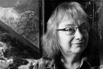 Black and white photo of author looking slightly to the right with a relaxed friendly expression. She has hair that just touches her shoulders and wears glasses and an open necked shirt. Behind her could be a window, could be a picture...