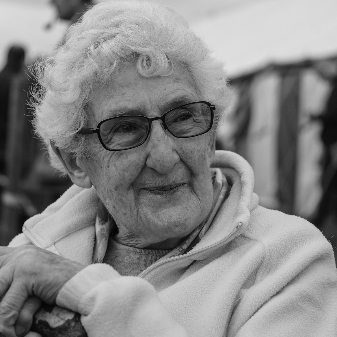 Monchrome photo of the author, looking to her left. She has white curly hair and one curl has fallen forward over her forehead. She is wearing a cosy fleece-type jacket and black framed glasses. She has a faintly impish smile.
