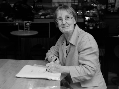 The author is pictured in monochrome sitting at a cafe table, pen in hand and a manuscript in front of her. She is looking at the photographer with a mischievous smile. She has short hair and glasses and is wearing a smartish jacket.