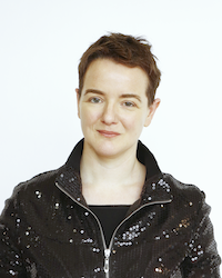 A full colour head and shoulders picture with the face square on looking the viewer right in the eye. She is smiling very slightly. A youngish woman with a boyish haircut, a clear open forehead, dark brown hair and eyebrows, blue eyes. She is wearing a glittery jacket, zipped open at the neck, and below it a plain black t-shirt with a straight neckline. No  jewellery of any sort.