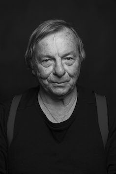 Black and white photo, head and shoulders. Poet is standing against a black background and wearing a black tee-shirt and braces. His face seems to radiate light and he has an expression that could be the start of a smile.